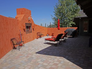 Santa Fe style outdoor area with stucco wall with built in fireplace