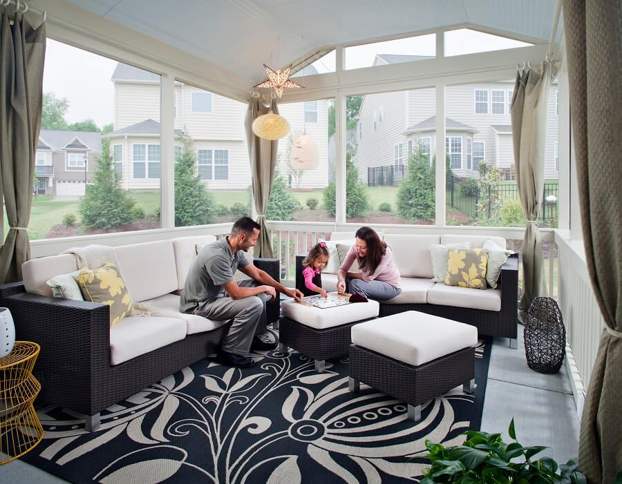 Family playing board game on cozy screened porch