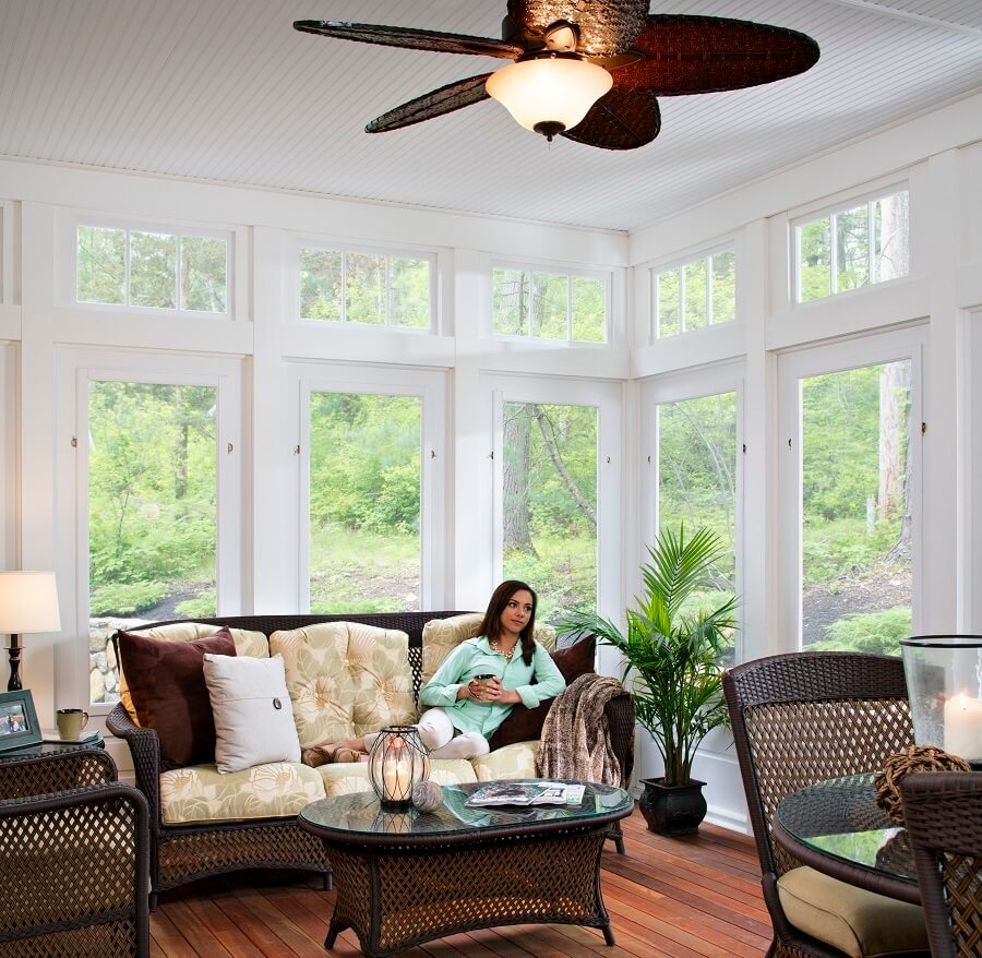 Cozy sunroom with lady sitting on couch with a mug