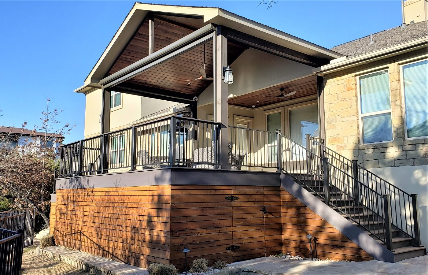 Side view of covered porch and deck with railing