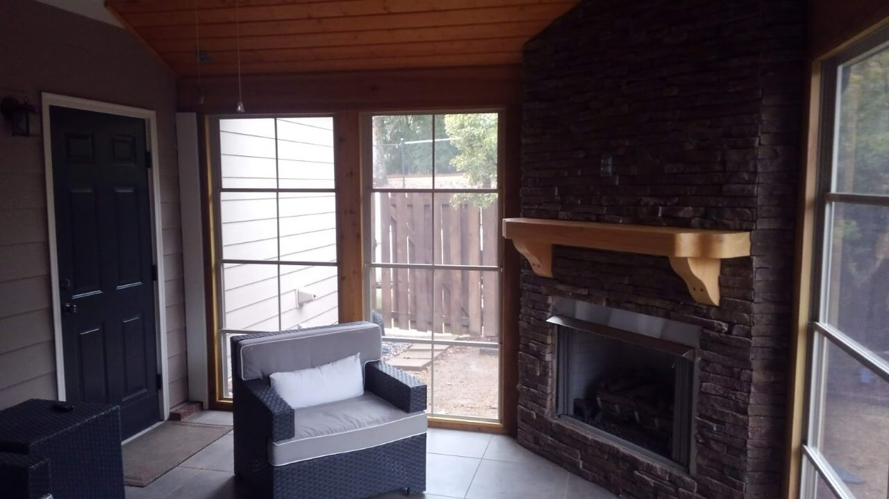 Three season room seating area and outdoor fireplace