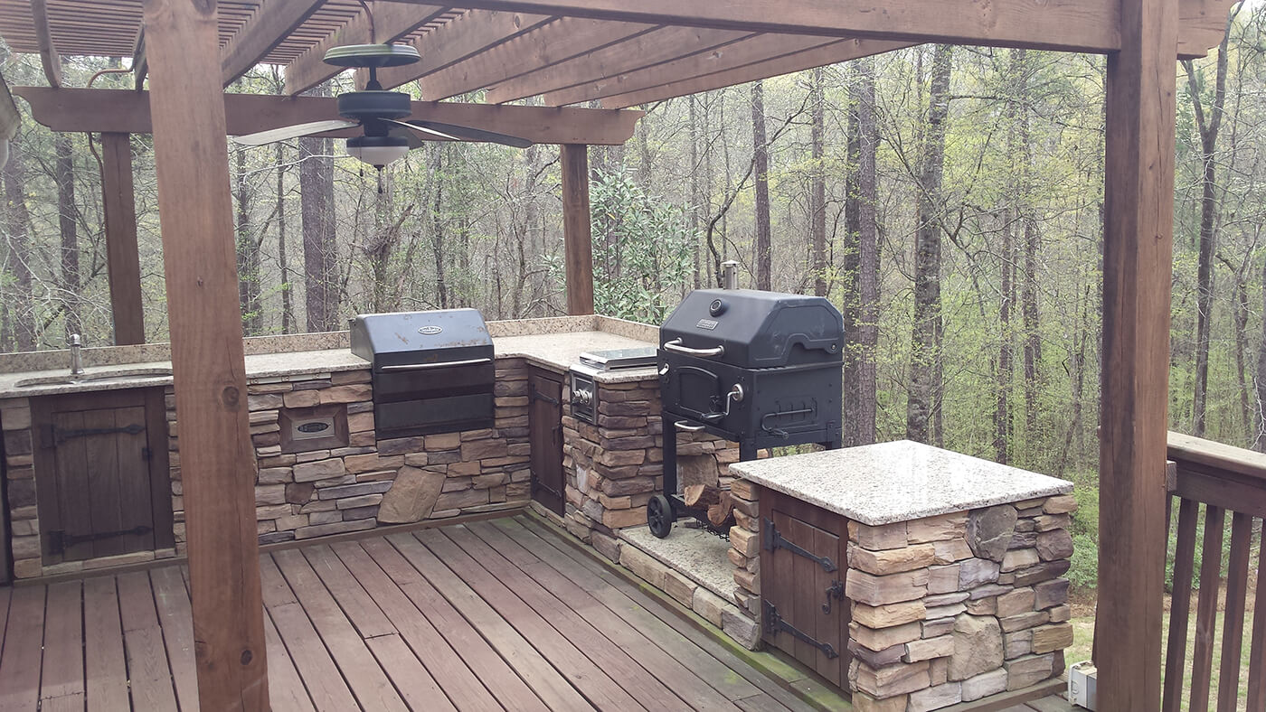 Custom backyard wood deck with pergola and outdoor kitchen