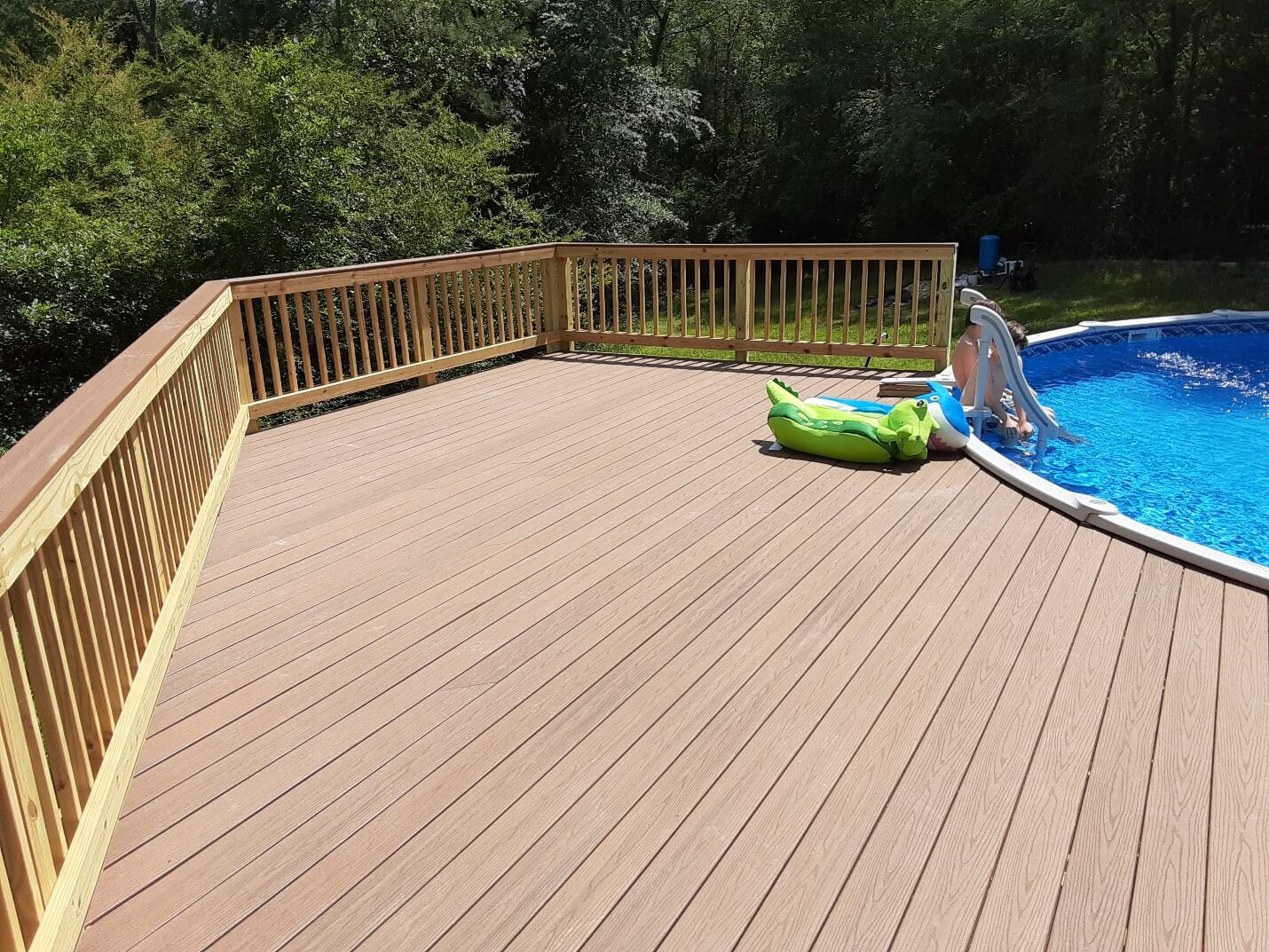 Custom poolside deck with kids sitting by the pool