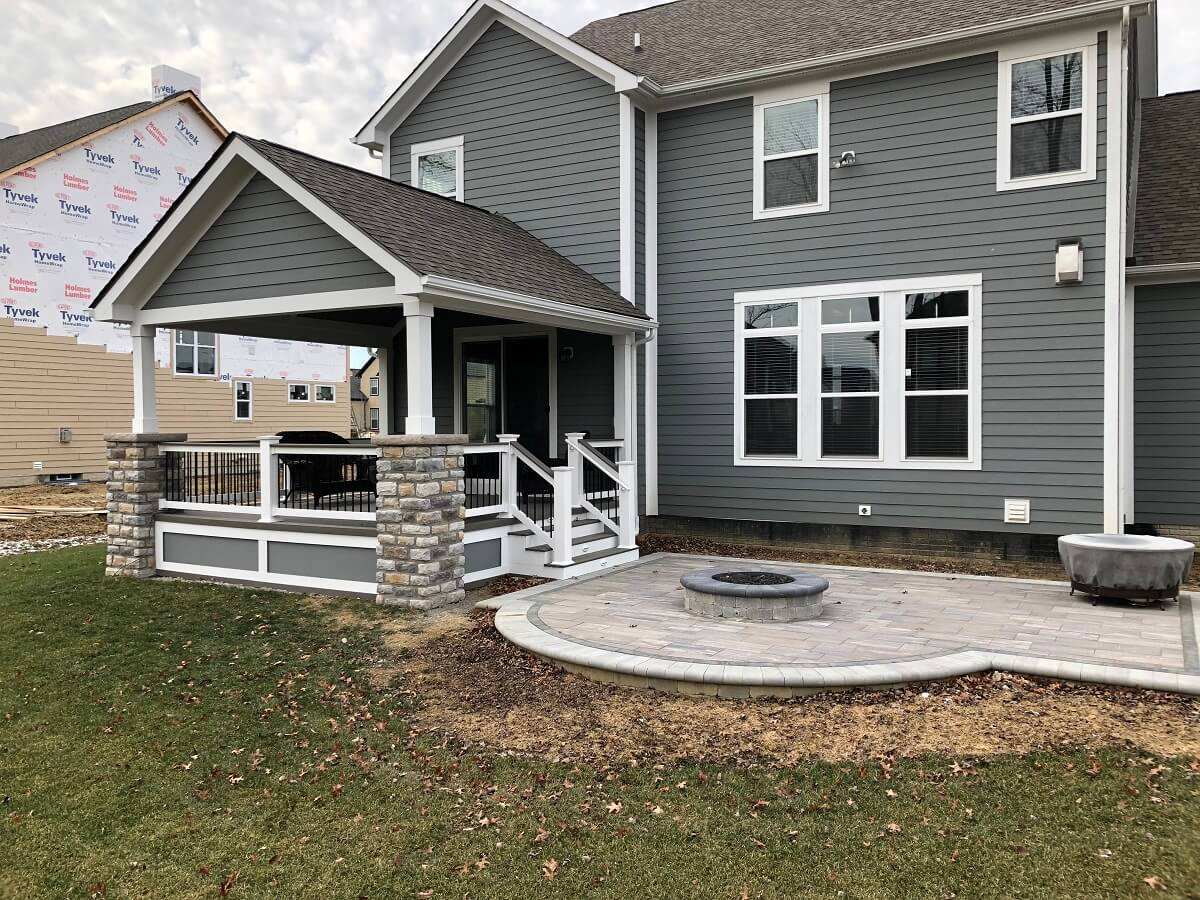 Custom backyard covered porch and patio with fire pit