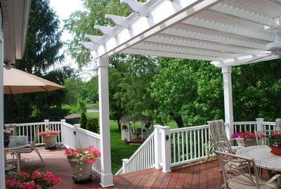 Custom backyard wood deck with white pergola and railing