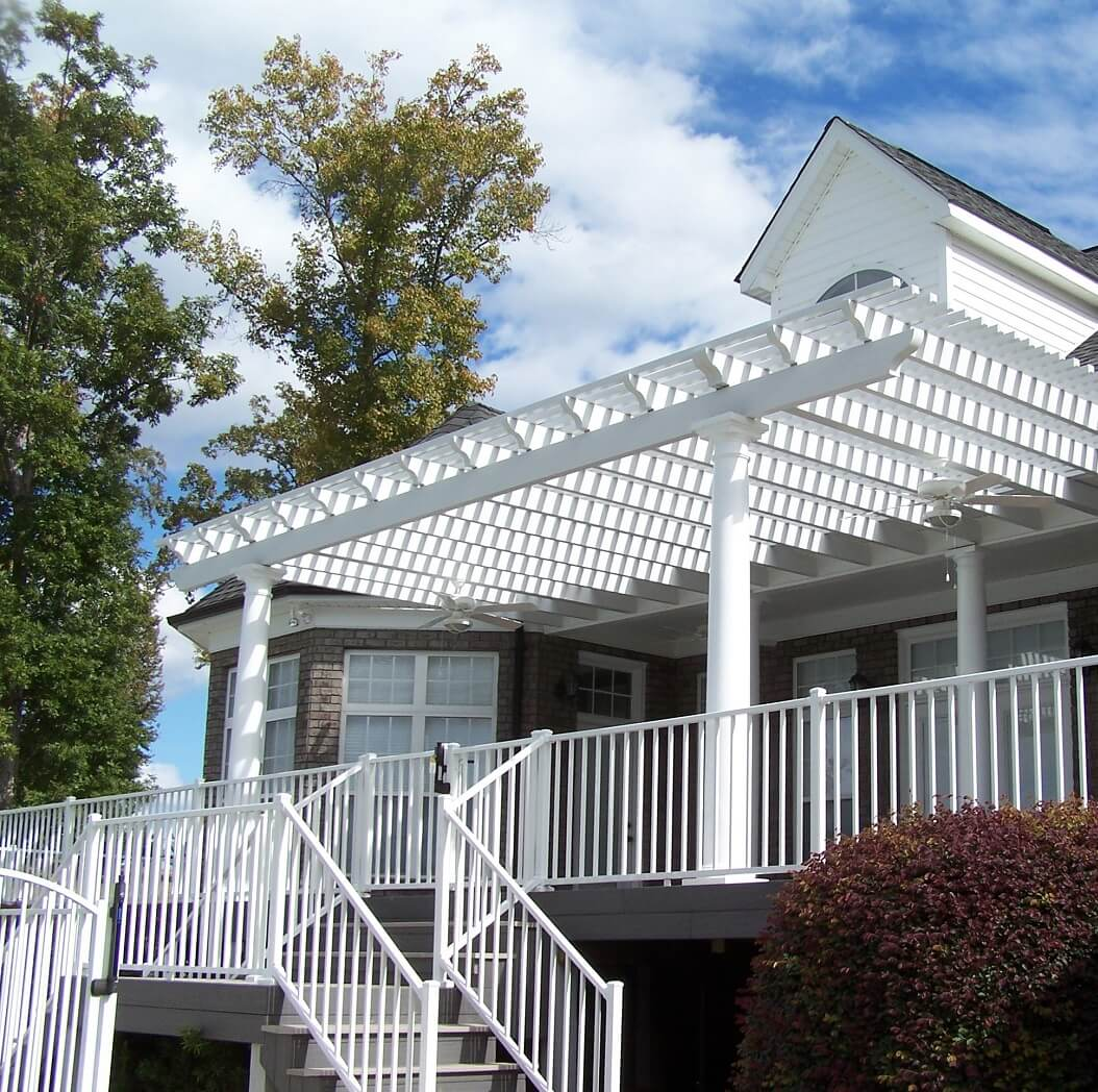 White pergola on deck with railing and staircase