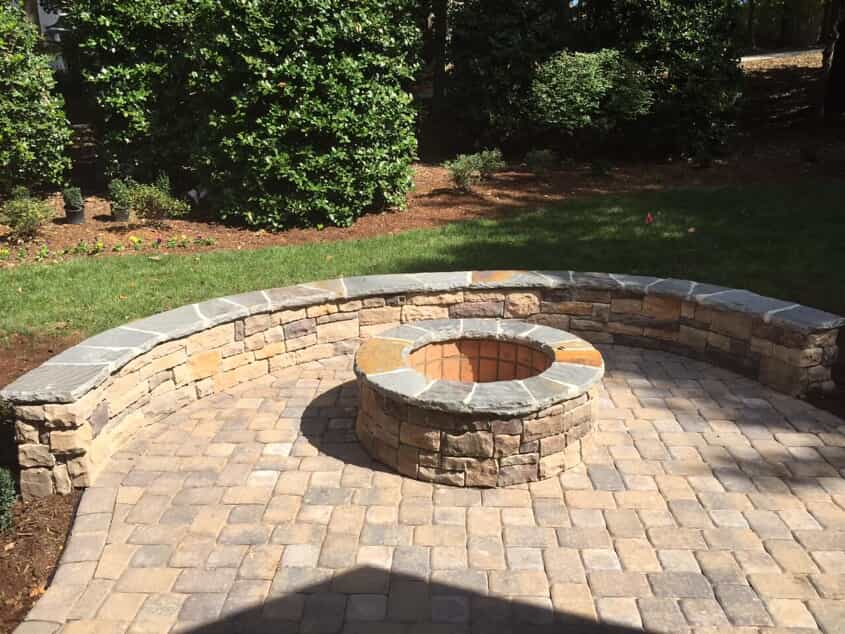stone patio with built in firepit and sitting wall