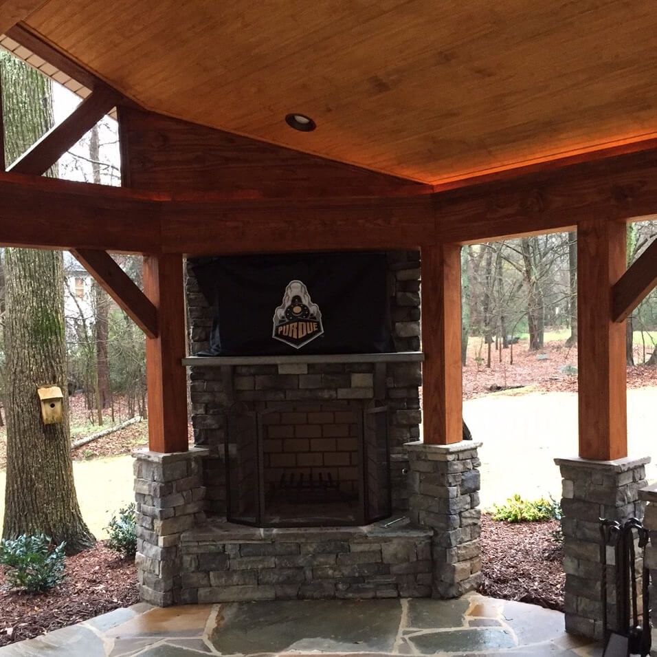 Covered outdoor space with a built in fireplace