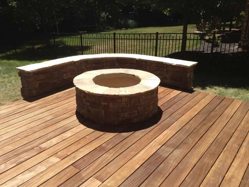 deck with fire pit and seating wall