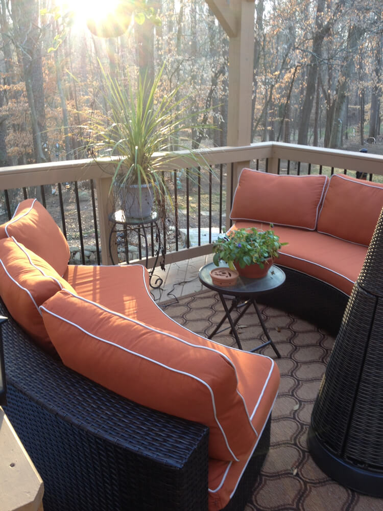 Waxhaw back porch with plants and furniture with orange cushions