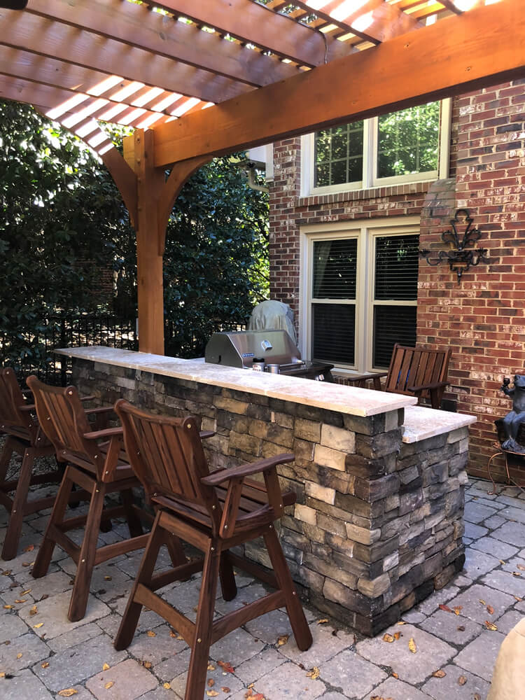 Custom patio with outdoor kitchen, bar counter and pergola