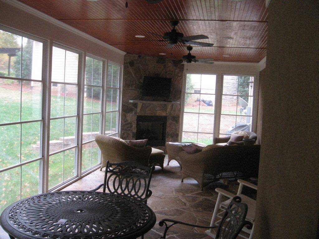 Custom porch with full wall windows and outdoor fireplace