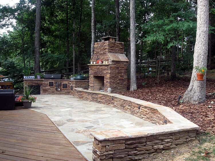 stone patio with seat wall, outdoor kitchen, and fireplace