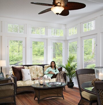 four season room with lots of windows and woman sitting on couch