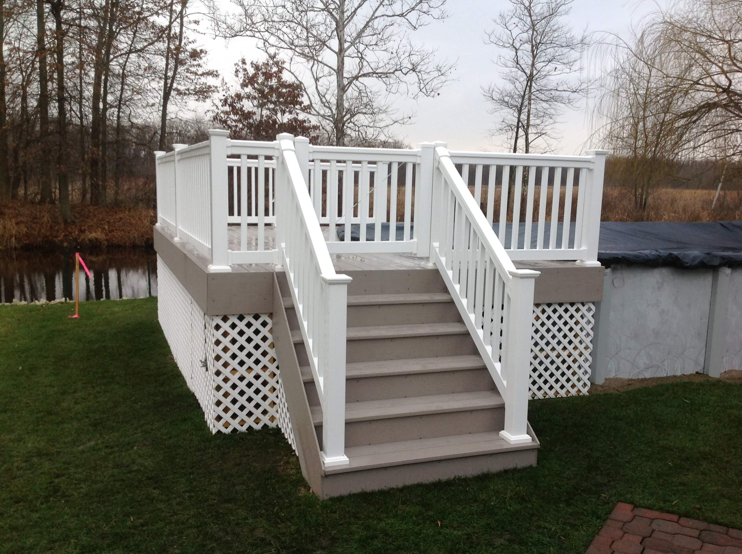 Custom backyard deck with white railing and staircase