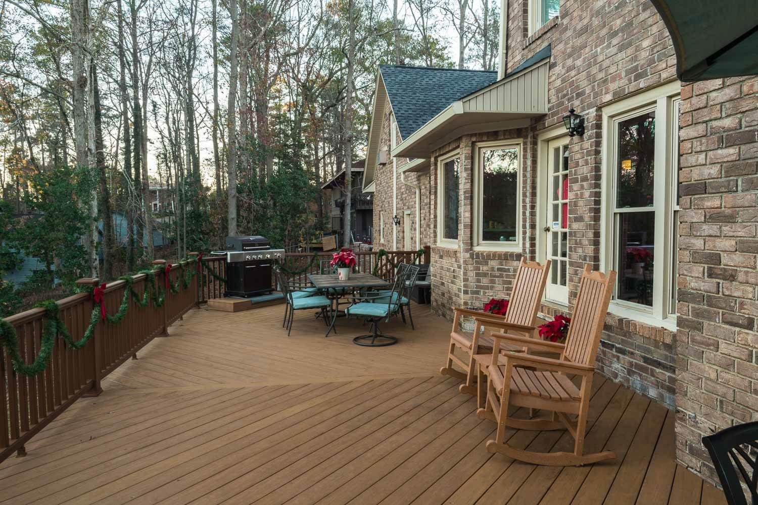 Custom backyard deck with outdoor kitchen, dining area and rocking chairs