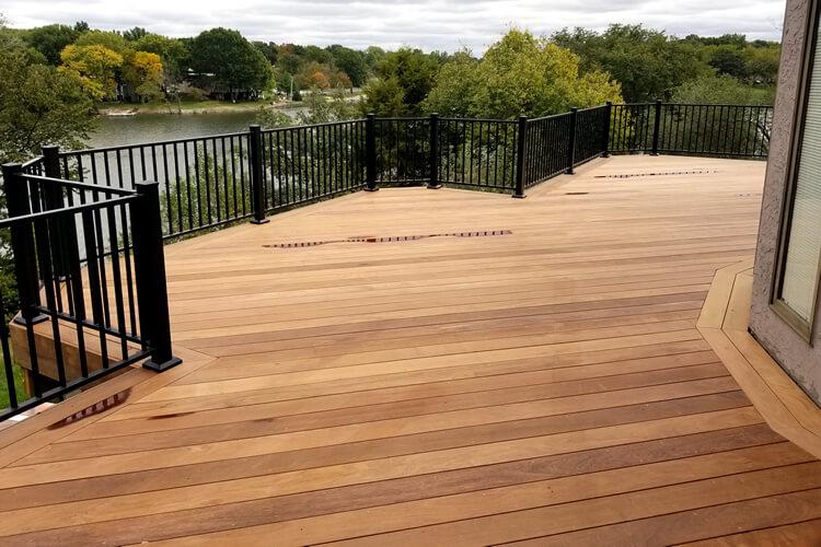 Wood deck with black railing.