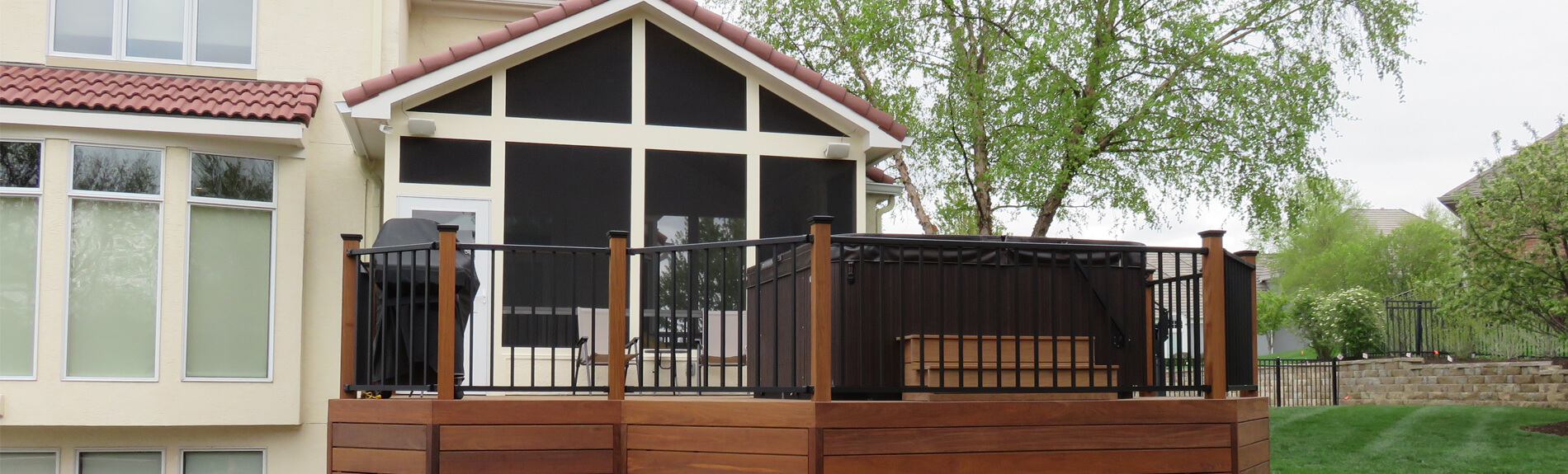 Backyard screened porch and deck with outdoor kitchen and hot tub