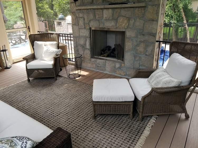 Custom outdoor fireplace and lounge area on screened porch