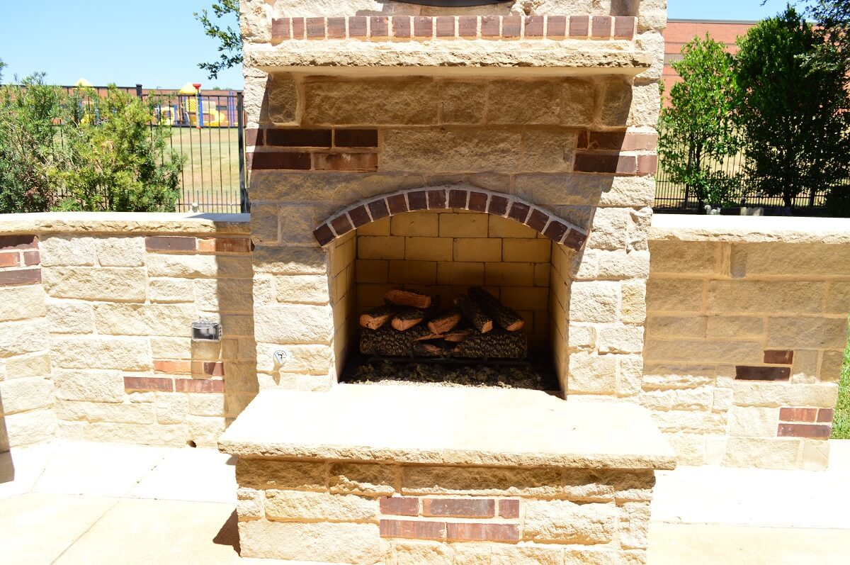Outdoor kitchen fireplace with gas log