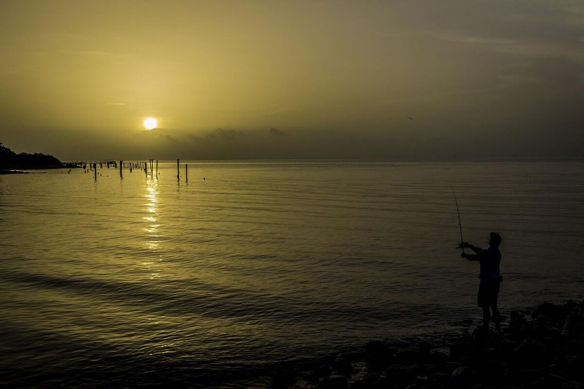man fishing on sea on sunrise