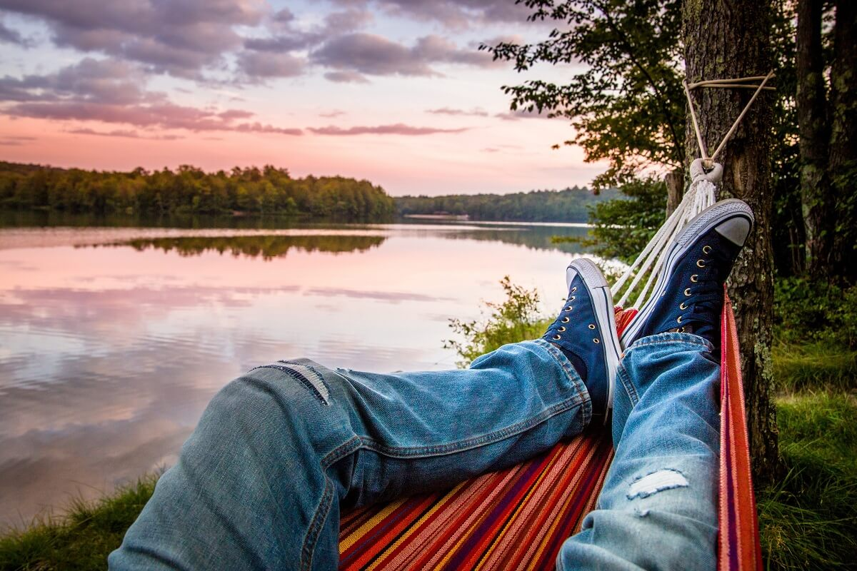 person in hammock with lake view