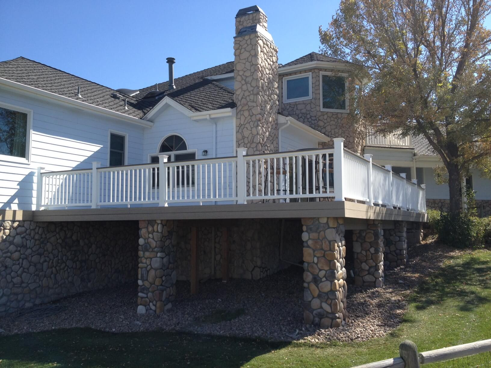 Custom elevated deck with railing and stone columns